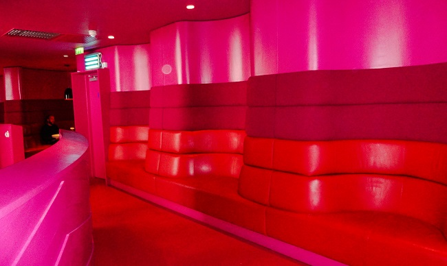 The pink and red seating at the back of the Rotunda Bar.