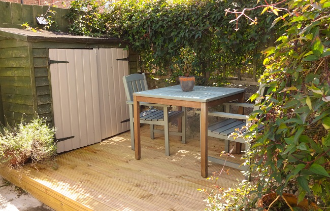 The back yard with new decking and recycled furniture. The shed is a bit ramshackle, especially since we lifted it to fit the decking, but could be handy for tenants.